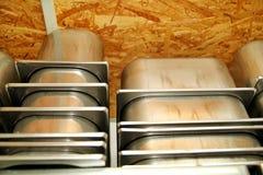 De containers van de staaldienst voor roomijs op stapels op de plank wordt ingepakt die Industriële voorbereiding van romig roomi royalty-vrije stock foto's