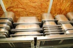 De containers van de staaldienst voor roomijs op stapels op de plank wordt ingepakt die Industriële voorbereiding van romig roomi stock foto's