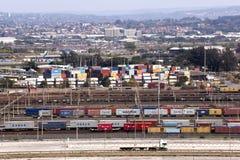 De containers vormden en stapelden bij Haveningang een rij Royalty-vrije Stock Afbeeldingen