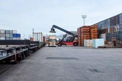 De containerstapelaar maakt vrachtwagens leeg stock fotografie