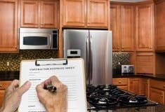 De contractant vult raming voor moderne keuken in stock afbeelding