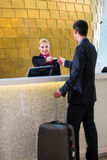 De controle van de hotelreceptionnist bij de mens die zeer belangrijke kaart geven Stock Foto