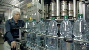 De controle van een productielijn voor het bottelen van mineraalwater in flessen stock videobeelden