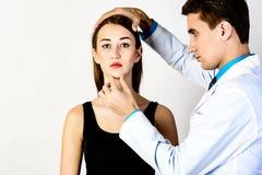 De controle van de gezichtshuid vóór plastische chirurgie Schoonheidsspecialist wat betreft vrouwengezicht stock fotografie