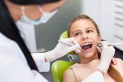 De controle van tanden op het kantoor van de tandarts Tandarts die meisjestanden onderzoeken Royalty-vrije Stock Foto