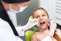 De controle van tanden op het kantoor van de tandarts Tandarts die meisjestanden onderzoeken Royalty-vrije Stock Afbeelding