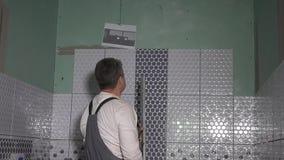 De controleniveau van de bouw hoofdmens van nieuwe muurtegels met het nivelleren van hulpmiddel stock video