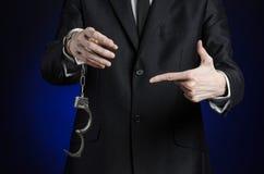 De corruptie en de omkoperij als thema hebben: zakenman in een zwart kostuum met handcuffs op zijn handen op een donkerblauwe geï stock afbeelding