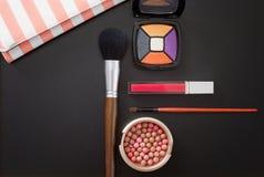 De cosmetischee producten en maken omhoog toebehoren op zwarte achtergrond Hoogste mening en exemplaarruimte De zomerkleuren Bors Royalty-vrije Stock Fotografie