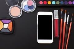De cosmetischee producten en maken omhoog toebehoren op zwarte achtergrond Smartphone met het lege scherm Hoogste mening en exemp Royalty-vrije Stock Afbeeldingen