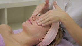 De cosmetologisthanden smeren het jonge vrouwelijke gezicht met het hydrateren van room in luxury spa salon in stock video