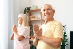 De couples d'exercice namaste supérieur de soins de santé ensemble à la maison Image stock