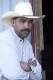 De cowboy leunt op deurframe. stock afbeelding