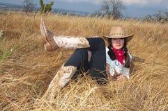De cowboy van de vrouw ontspant op een gebied Stock Foto