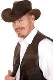 De cowboy in vest en de hoed kijken grijnslachglimlach Royalty-vrije Stock Fotografie