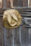 De cowboyhoed van het stro en doorstaan hout Stock Foto