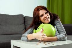 De creatieve achtergrond, een mooi meisje koestert een spaarvarken in de vorm van een groen varken Het concept besparingsgeld, be stock afbeeldingen