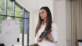 De creatieve bedrijfsvrouwengebaren bespreekt en tonend iets op computertablet met glimlach terwijl haar medewerkers stock videobeelden