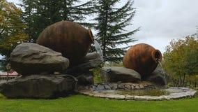De creatieve die fontein van de kleikruik door reusachtige die stenen wordt omringd in groen park, art. worden gevestigd stock footage