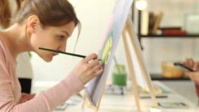 De creatieve eigentijdse schilder schildert het kleurrijke abstracte schilderen Close-up van het schilderen proces in kunstworksh stock footage