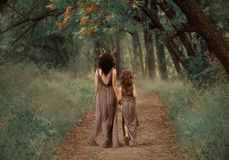 De creatieve familiefoto van donkerbruine moeder en blonde dochter, fauns houdt handen en gaat diep in het bos langs stock afbeeldingen