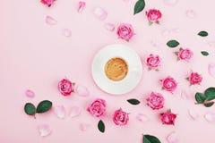 De creatieve kaart met koffiekop, groene bladeren en mooie roze nam bloemen op de bovenkantmening van de pastelkleurlijst in vlak royalty-vrije stock afbeelding