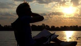 De creatieve Mens leest en denkt over Zijn Nota's Zittend op een Riverbank in slo-Mo stock video
