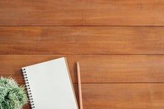 De creatieve vlakte legt foto van werkruimtebureau Achtergrond van de bureau de houten lijst met open spot op notitieboekjes en p Stock Fotografie