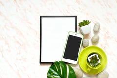 De creatieve Vlakte legt marmeren bureau met wit leeg kader voor tekst, telefoon, kop, stenen en succulents achtergrond Royalty-vrije Stock Afbeeldingen