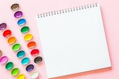 De creatieve vlakte legt van waterverfpaletten en notitieboekje Kunstenaarswerkplaats op een roze pastelkleurachtergrond vector illustratie
