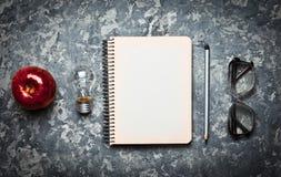 De creatieve werkruimte van de schrijver is inspirerend om te creëren Ik heb een idee Blocnote, pen, gloeiende bol, appel, glazen Stock Fotografie