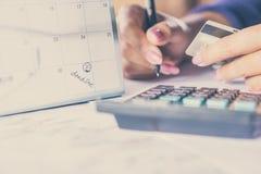 De creditcard die van de handholding haar maandelijkse uitgaven met uiterste termijnkalender berekenen stock afbeeldingen