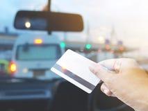 De creditcard van de handholding over vage achtergrond van auto bij loon t royalty-vrije stock foto