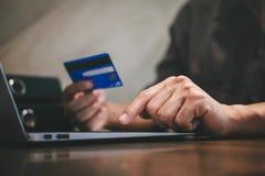 De creditcard van de zakenmanholding en het typen op laptop voor online het winkelen en betaling maken een aankoop op Internet, o royalty-vrije stock foto's
