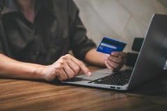 De creditcard van de zakenmanholding en het typen op laptop voor online het winkelen en betaling maken een aankoop op Internet, o stock foto