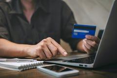 De creditcard van de zakenmanholding en het typen op laptop voor online het winkelen en betaling maken een aankoop op Internet, o stock afbeelding