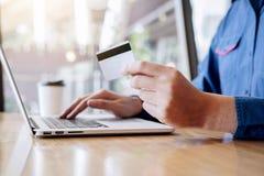 De creditcard van de zakenmanholding en het typen op laptop voor online het winkelen en betaling maken een aankoop op Internet, o stock foto's