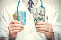 De creditcards van de artsenholding in zijn linkerzijde en de dollars van de V.S. in zijn rechts Royalty-vrije Stock Fotografie
