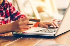 De creditcards van de vrouwenholding en de mobiele telefoons winkelen nu stock foto's
