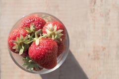 De cristal de fresas se coloca por completo en un fondo de madera Foto de archivo