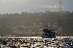 De cruiseboot van Istanboel Bosphorus bij zonsondergang op wazig Stock Afbeeldingen