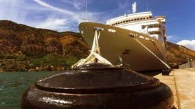 De cruisevoering wordt bij de pijler in de haven in een baai vastgelegd door bergen wordt omringd die stock afbeelding