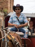 De Cubaanse mens drijft een paard getrokken taxi stock foto's