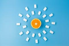 De cubes frais en sucre orange et beaucoup blanc autour sur le fond bleu Vue supérieure Images stock