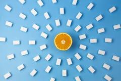 De cubes frais en sucre orange et beaucoup blanc sur le fond bleu Photographie stock