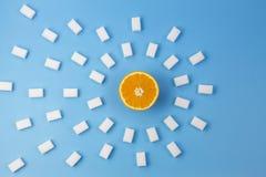 De cubes frais en sucre orange et beaucoup blanc sur le fond bleu Images stock