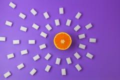 De cubes frais en sucre orange et beaucoup blanc sur le fond pourpre Photographie stock libre de droits