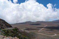 De cumuluswolken vormen zich in de passaatwind over de weg aan de vulkanische krater Piton DE La Fournaise op het eiland van La R stock fotografie