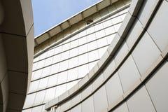 De Curvy moderne bouw in zonnige hemel stock afbeeldingen