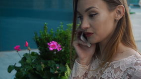 De Cutievrouw zit in de straat en het spreken op mobiele telefoon stock videobeelden